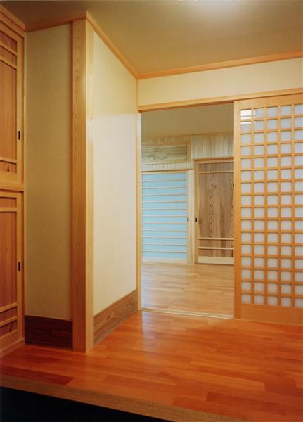 玄関は御影石張り。室内の床はサクラの無垢材。室内建具も無垢の木を使ってのオリジナルデザイン。