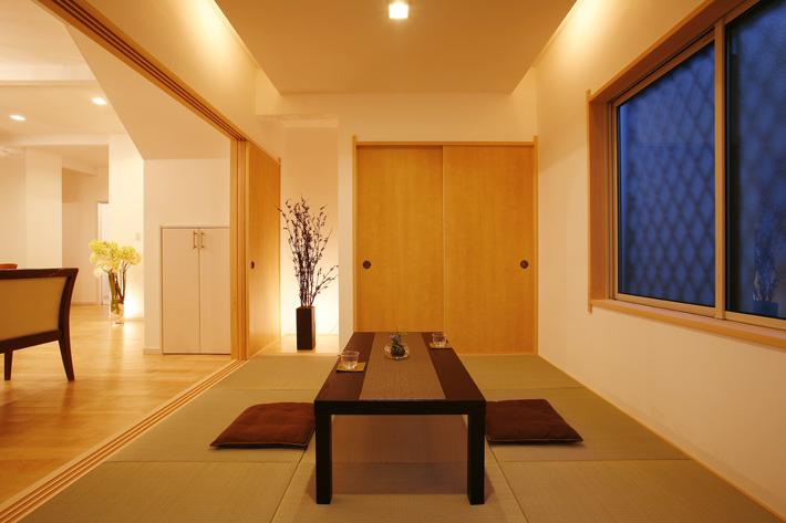 リビングと同じ漆喰の壁を施し、雰囲気の繋がりをもたせた和室。天井の照明がアクセント。