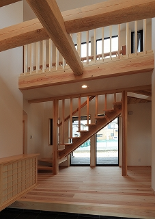 玄関ホール。 スケルトンの階段越しにウッドデッキが望める。