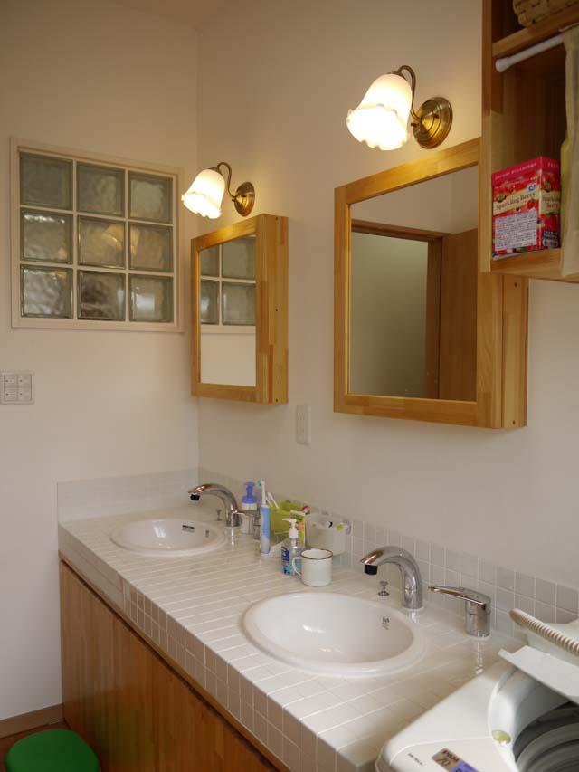 2ボールの洗面台は白いタイルを使ったこだわり仕様。鏡の裏は収納になっていて、見せると仕舞うをおしゃれに演出。