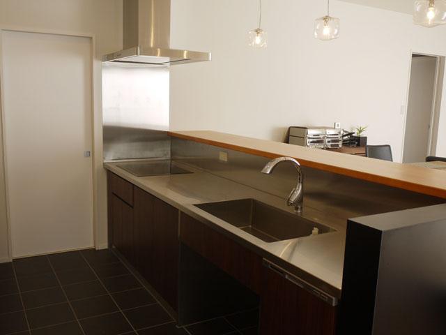 I 様邸のキッチンは、奥様のこだわりを詰め込んだ素敵空間。キッチンの奥にユーティリティースペースを設け、食器棚や冷蔵庫などをそちらに収納することですっきりとした空間が広がります。また、キッチンのフロアをタイル貼りにすることでよりスタイリッシュな印象に。
