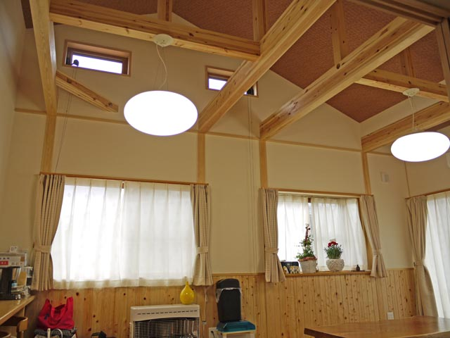 勾配天井を利用し梁をみせたリビング。窓の配置や照明にもこだわった光あふれる空間です。