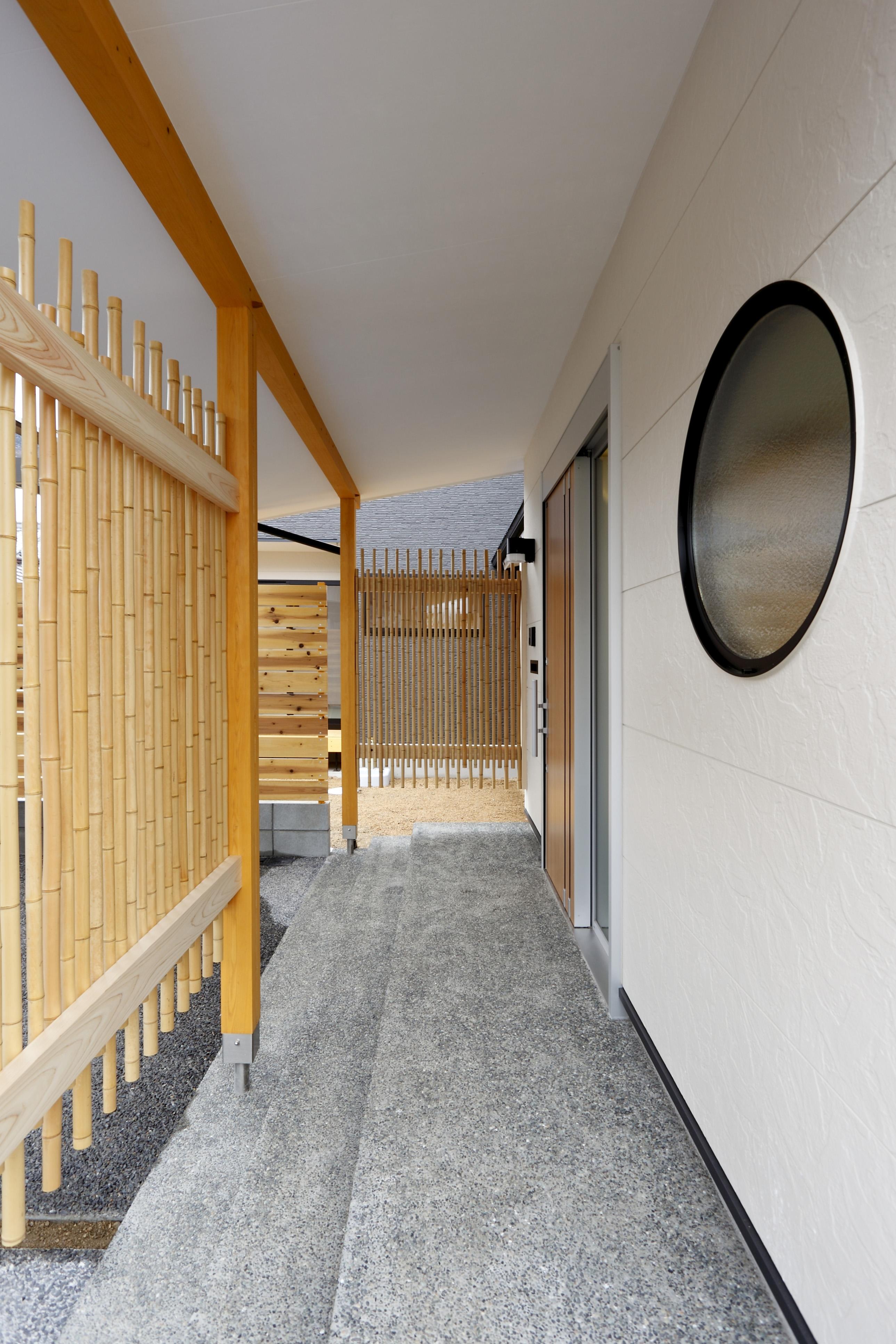 玄関までのアプローチには住まい手の心遣いが表れる。玄関を入るまでの空間にも竹や丸窓で穏やかな空気をつくる