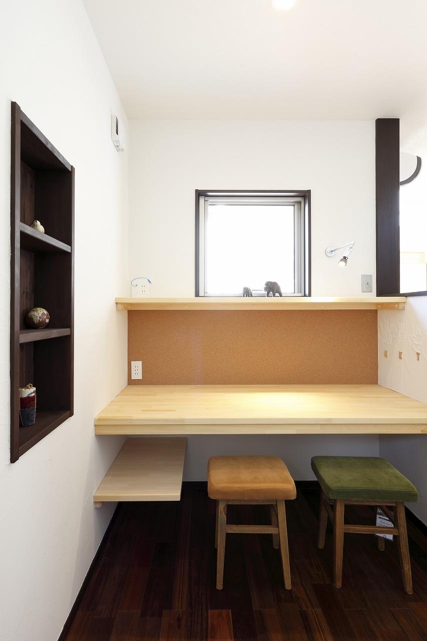 キッチン脇には奥様の家事兼用プライベートコーナー。正面のコルク貼りのファミリーボードには家族の写真や予定表を