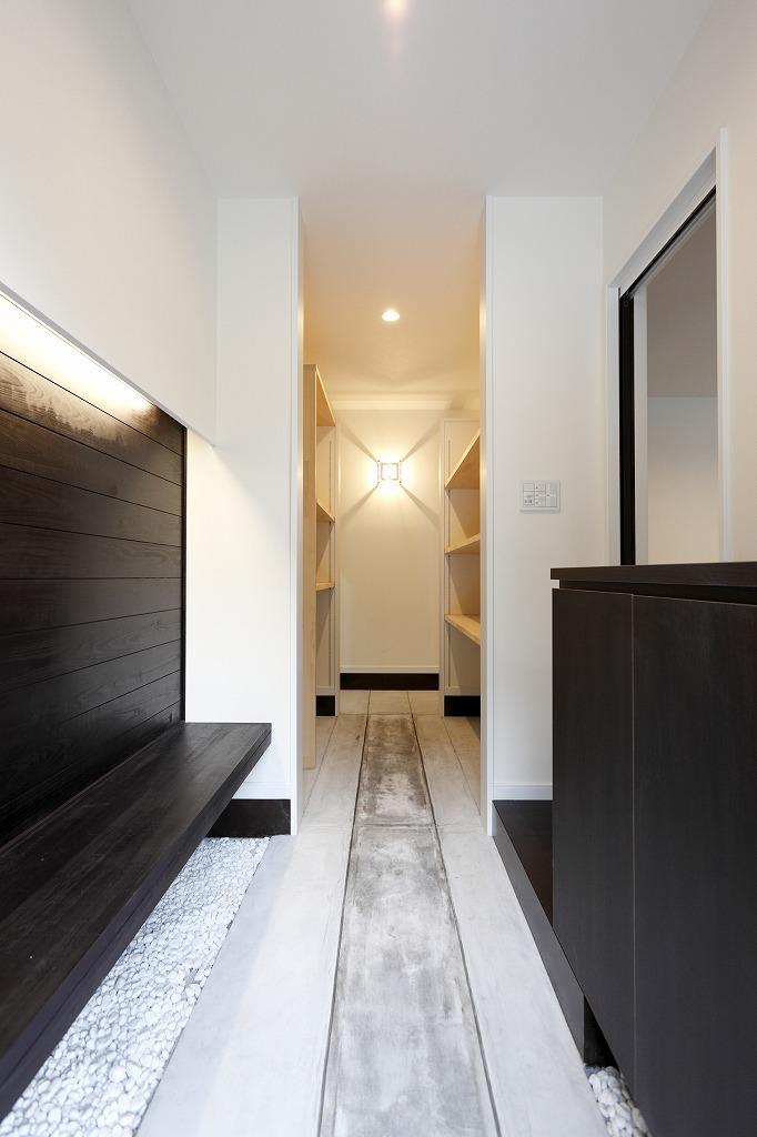 玄関からオープン収納を通って右はリビング左はガレージ。正面壁の照明器具は掛谷建設のロゴマーク入りのオリジナル
