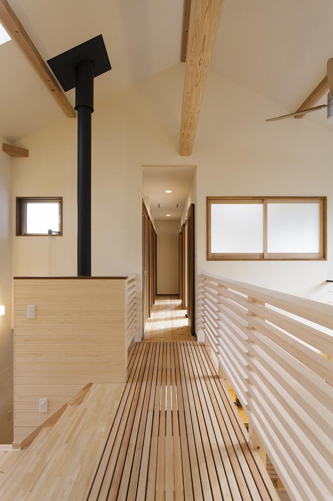 スノコ状の床の開放廊下は薪ストーブのぬくもりを隅々に。左の広い階段は中2階の大画面テレビを観る子どもたちの観客席に