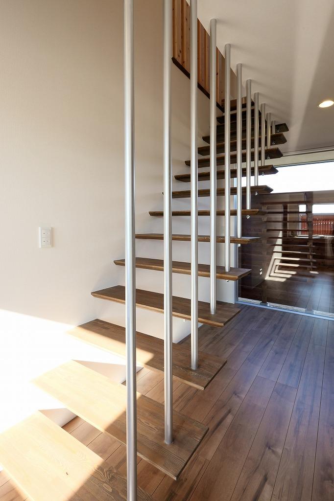 玄関を入ると目に飛び込むオープン階段。奥には浴室からも眺める事の出来る坪庭