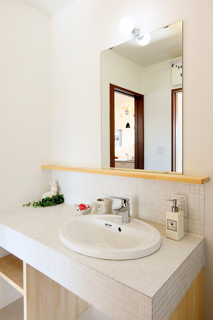 洗面化粧台はホワイトのタイルで清潔感溢れる。毎日使う場所だから、お手入れしやすくシンプルに
