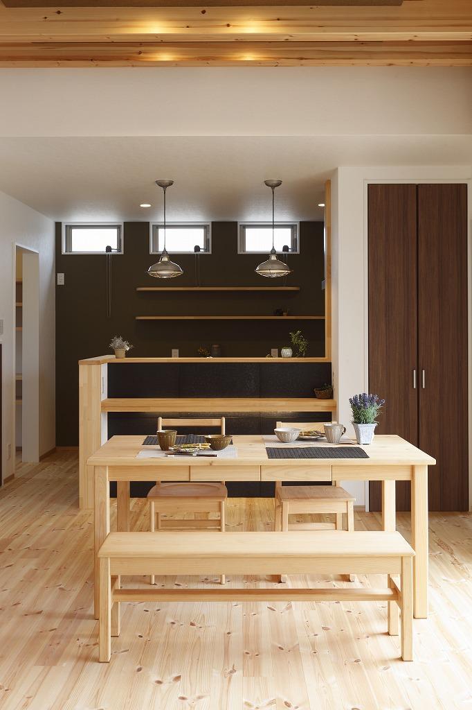 リビングと繋がるダイニングキッチンはシックに。カウンター腰壁タイル、背面飾棚、照明器具と落ち着いた雰囲気に