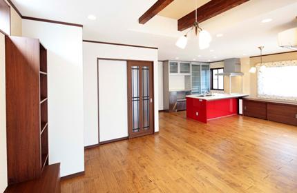 """無垢の床板を敷き詰めたリビング・ダイニング。ナチュラルな空間に、赤いキッチンがひときわ鮮やかに映えています。 また、壁は2種類の壁紙で仕上げました。1つの部屋でも、2つの壁紙を用いることで夜に照明を灯したときに違った表情を楽しむことができます。 天井には、木の表情がアクセントとなる""""あらわし梁""""を採用しました。"""