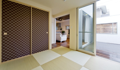 壁に囲まれたプライベートなテラスとつながるタタミ室は、いつでもゴロンと横になれます