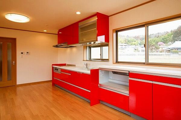 赤いキッチンが印象的なリビング