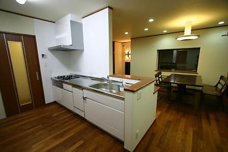 キッチンは位置を変えて対面型に。濃い床に、白のシステムキッチンでシックにコーディネート。