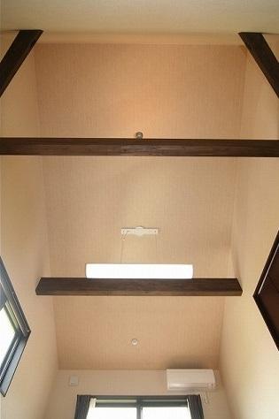 勾配天井にダイナミックな梁を現した寝室。濃い色で落着いた雰囲気に。