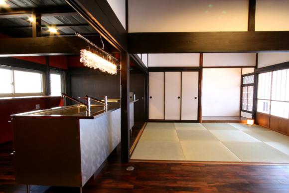 メタリックでシャープな印象のアイランドキッチンに差鴨居や漆喰の懐かしさが調和しています。