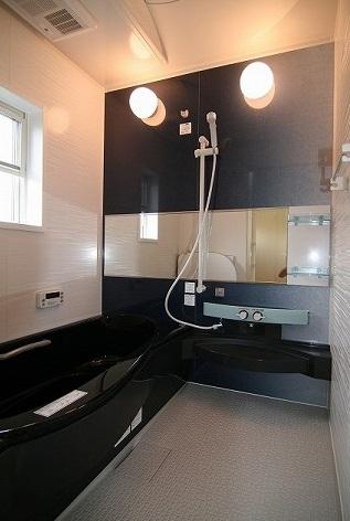照明の明かりが幻想的な雰囲気を醸し出します。浴室には黒色の浴槽でお洒落に演出。
