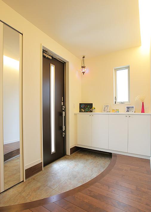 面積以上にゆったり感じられる玄関ホール。間接照明とアール框(かまち)が優美な雰囲気を漂わせる。