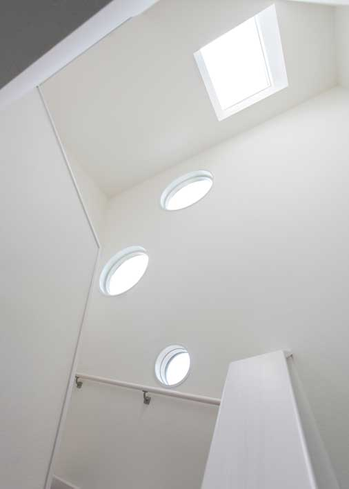 旦那様の家づくりにおける条件のひとつであった丸窓は2階から3階へ繋がる壁面に設置。スタイリッシュな外観の中にやわらかい雰囲気を演出する。また、天井窓は建物の構想段階で担当営業から提案され、採用された。曇りの日でも明るいとご夫婦のお気に入りだそうだ