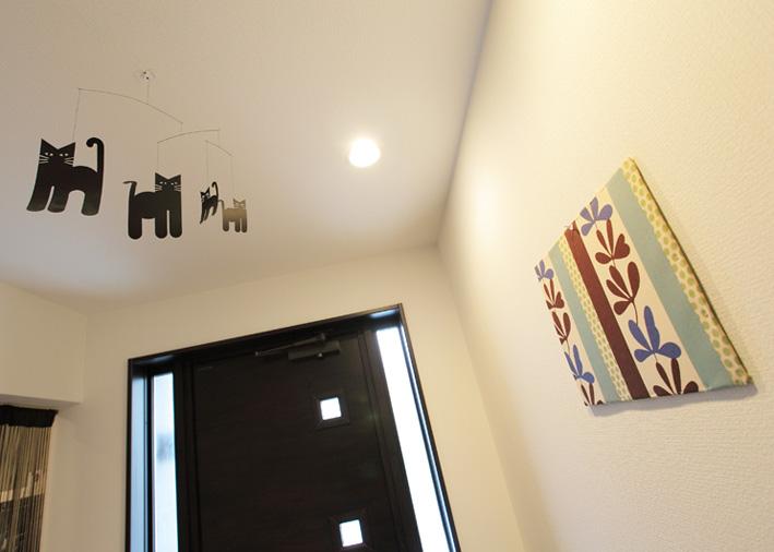 ファブリックパネルや天井の飾りなど家づくりのこだわりが玄関から伝わってくる。