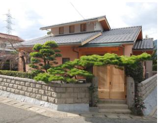 ゆるやかな勾配の瓦屋根が、日本の家らしい佇まいを演出。赤味がかった個性的な外壁が、わが家らしさを生み出しています。