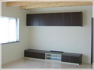 白い床と壁に引き立つ黒いホームシアター。天井の化粧梁が雰囲気を盛り上げます。