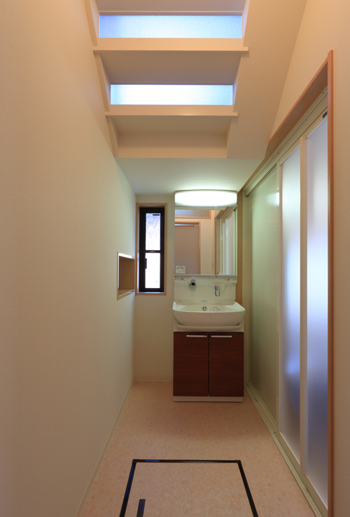 洗面脱衣室。 天井からの採光は階段の蹴上げを一部加工している。