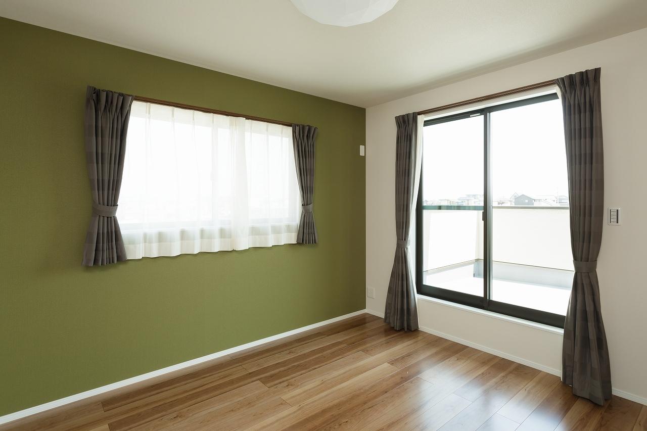 寝室はモスグリーンの壁が安らぎを演出
