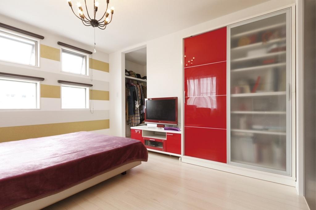 スクエア窓からやさしい陽光が差し込む寝室。2階の床にも風合い豊かな無垢材を使っている
