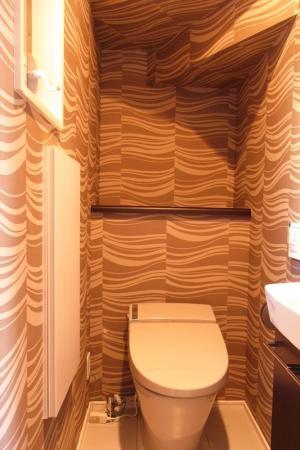 タンクレストイレの⾊をグレー⾊に、そして壁紙も便器の⾊に合わせ、グレー系で統⼀。その空間はまるでカ フェにきたような感覚に。