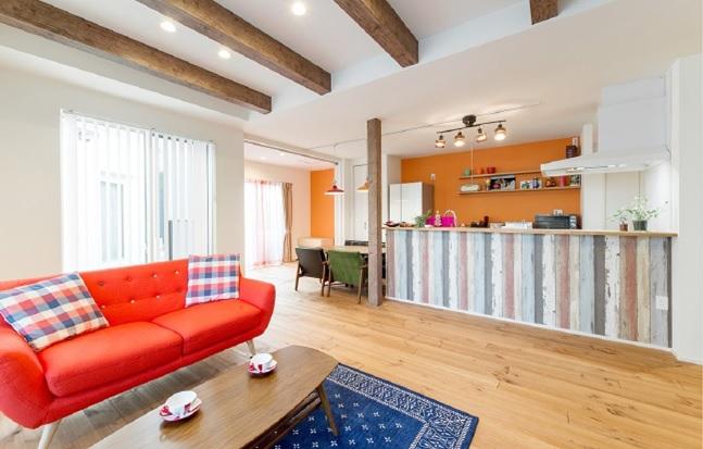 素朴な味わいのあるパインの無垢フローリングを採用し、折上天井に添わせた梁、キッチンカウンターやカップボード部分に使ったオレンジのアクセントクロスにより、カフェのようなインテリアを見事に表現しています