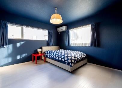 主寝室のクロスは壁にも天井にも落ち着いた紺色を選択し、モダンな印象の部屋に仕上げています
