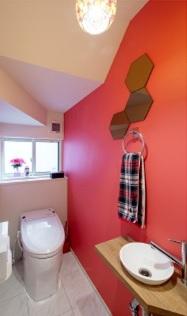 1階のトイレは赤のクロスを使って大胆に。洗面もカフェのようなオシャレなデザインを採用しています