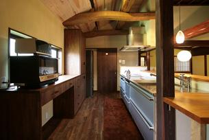 以前のキッチンは壁向きのL字型で、作業動線の悪く、寒さの問題がありました。吹抜天井で断熱施工を施し、明るさと暖かさを確保しました。虹梁とステンレスのキッチン、ウォールナットの床材が空間を引き締めます。