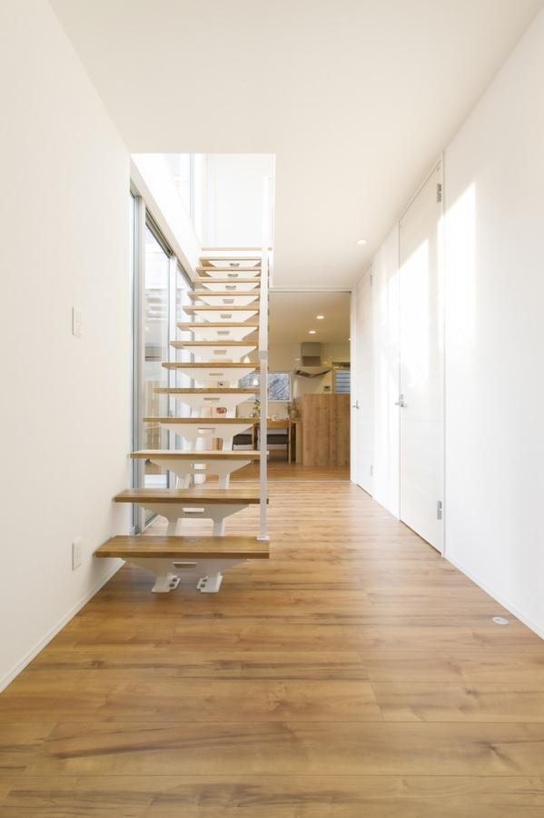玄関扉を開けるとこの風景が開ける。家具のような美しいストリップ階段が開放感を高める