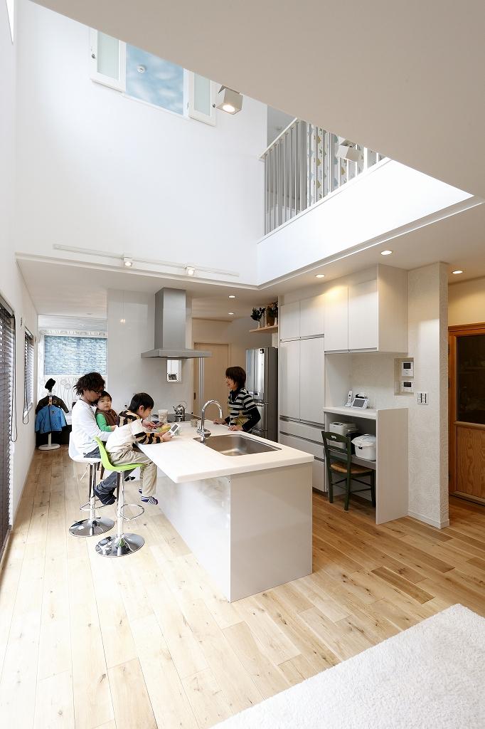 吹抜けから明るい光が差し込むキッチンを中心にしたLDK