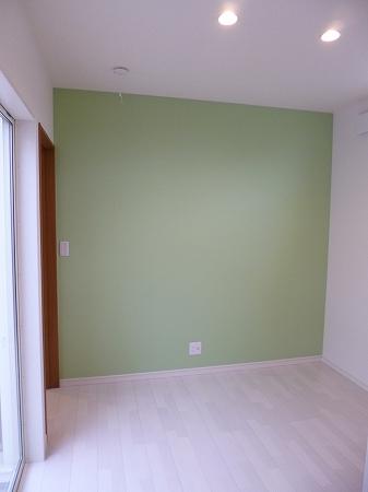 淡いグリーンのアクセントクロスが効いた洋室