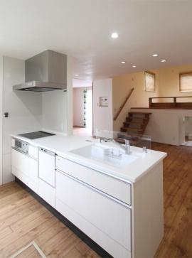 白で統一されたキッチン。シンクの前には、ガラス製の水はね防止スクリーンを設置。