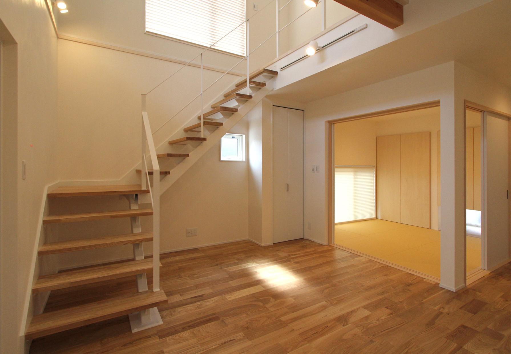 建物中央に吹抜けのリビングを配置し、壁面に沿ってオープン階段を付けるという思い切った構造は、切妻屋根のシンプルな外観デザインからは想像できない。1階には野球のバットにも使われるタモ材の無垢フローリングが使われている。