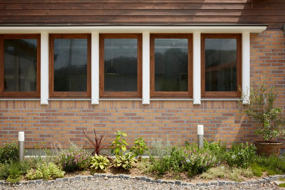 レンガ貼りの外壁に映える漆喰塗の窓飾り