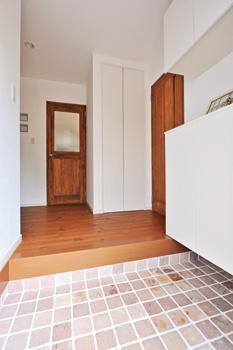 漆喰壁と特注⾊のパイン無垢材床が織りなす空間 へ誘う⽞関。LDKにつながるドアにもチェッカーガ ラスが アンティーク⾵のドアやランプにマッチした、味わい深いレンガ⾵の タイルを⽞関ポーチにセッティング。⾶び⽯や芝⽣と相まって雰囲気 の良いエントランスになっている