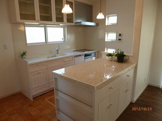 無垢扉のシステムキッチンと造作収納カウンターがあるこだわりのキッチンスペース。