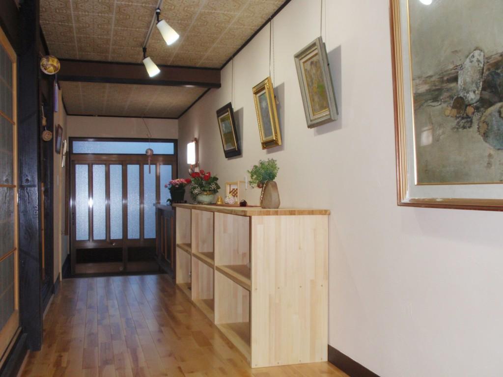 玄関 玄関ホールは集成材で造った棚を置き飾るスペースとして利用。壁面には額縁を飾ることで、玄関に入ると小物や額縁が目に入るギャラリーのような素敵な空間になりました。