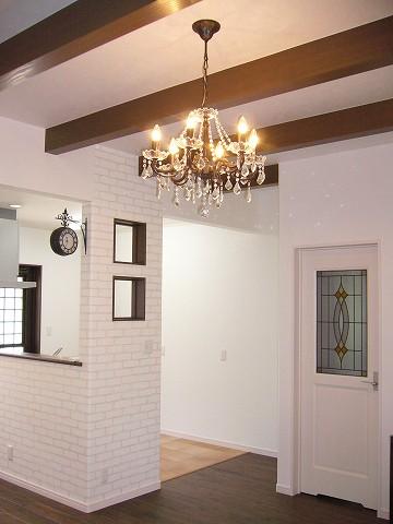 リビングダイニングの床は杉の無垢材、キッチンはフロアタイルを採用し、梁見せの天井とシャンデリアがいい雰囲気です。