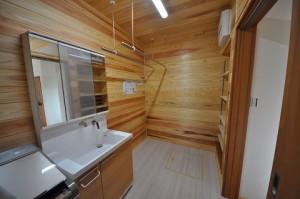 キッチン脇には杉を張った脱衣室。洗濯して、干して、たたんで、棚に収納という家事ラク動線。